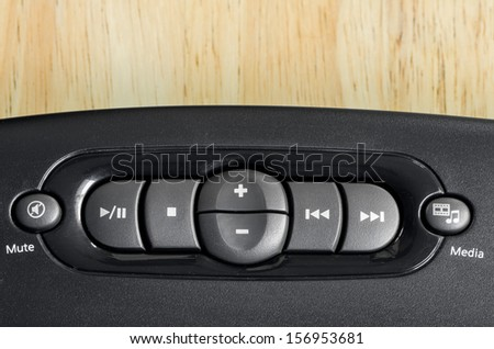 Close-up music player button of keyboard on wood table - stock photo