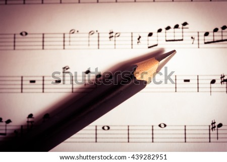 Close-up music sheets and pencils background. Musical concept background: macro view of white score sheet music with notes. Sheet Music Background Musical Notes with selective focus. - Vintage Tone.