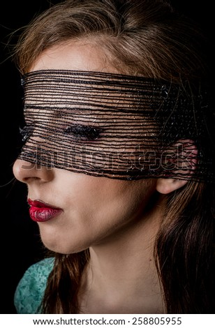 Close up Mysterious Pretty Woman with Black net on her Face Facing to the Left of the Frame on a Black Background. - stock photo
