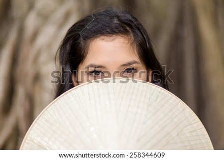 Close up Mysterious Young Woman Covering her Half Face with conical hat While Looking at the Camera. - stock photo