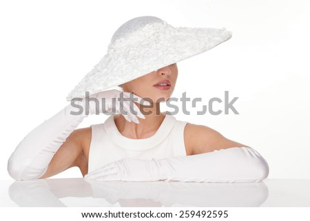 Close up Mysterious Young Woman in Elegant white Hat with glowes on - stock photo