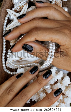 close up nails with manicure among sea stuff, shell, coral, starfish, african tanned hands - stock photo
