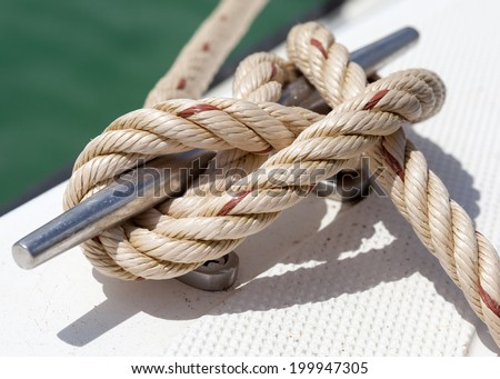 Close-up nautical knot rope tied around stake on boat or ship, boat mooring rope - stock photo