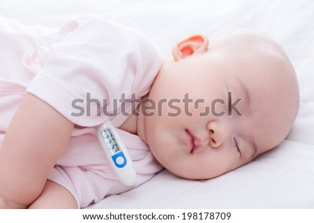 Close-up newborn baby sleeping with digital mercury thermometer - stock photo