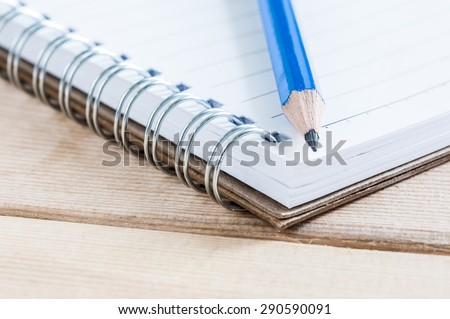 close-up notebook and pencil on wood table - stock photo