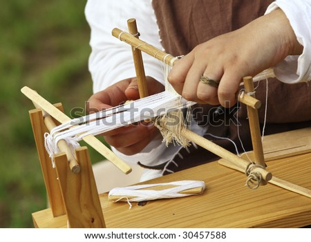 close up od ancient little loom and hands - stock photo