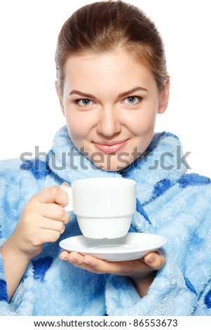 Close up od young female in bathrobe drinking a tea - stock photo