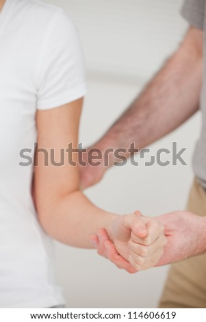 Close up of a a man stretching an elbow in a room - stock photo