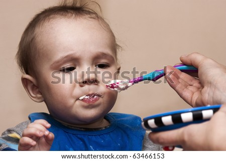 Close up of a baby boy being fed by he's mother, but not enjoying the porridge. - stock photo