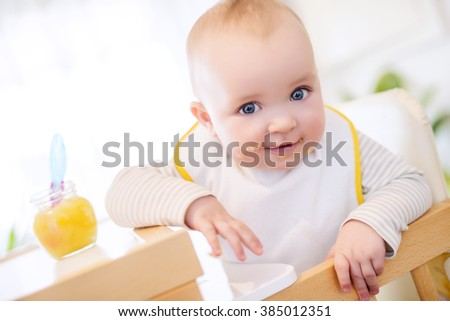 Close up of a baby boy in high chair.He is looking at camera - stock photo