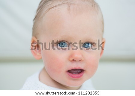 Close up of a baby having blue eyes in living room