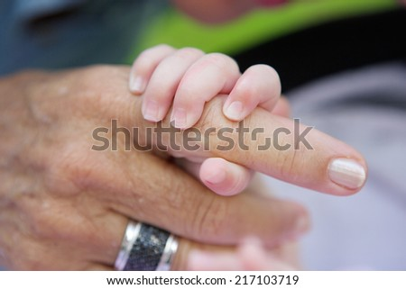 Close up of a baby holding grandmother's hand - stock photo