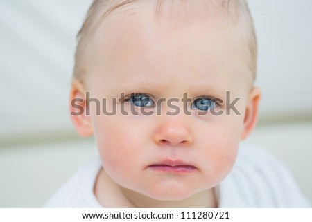 Close up of a baby looking at camera in living room - stock photo