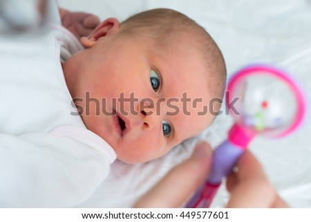 Close-up Of A Baby Looking At Rattle Hold By Her Mother - stock photo