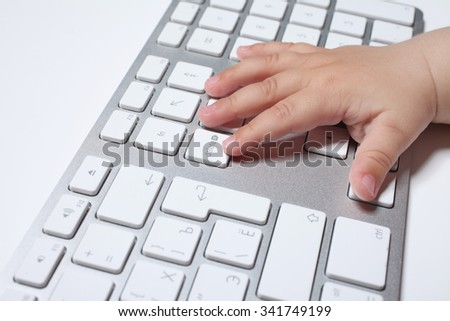 Close-up of a baby's hand using keyboard.