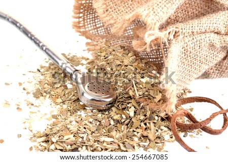 Close up of a bag with mate tea pouring out and a silver bombilla - stock photo