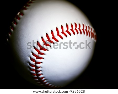 close-up of a baseball against dark background