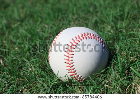 Close-up of a baseball on a grass field.