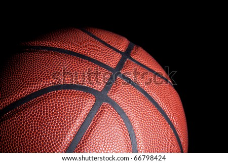 Close-up of a basketball with dramatic side lighting on a black background. - stock photo