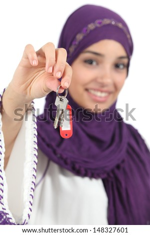 Close up of a beautiful arab woman holding a home keys isolated on a white background             - stock photo