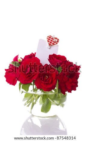 Close-up of a beautiful bouquet of red roses in a round glass vase. Isolated - stock photo