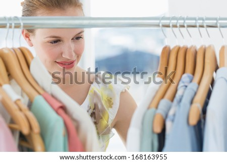 Close-up of a beautiful female customer selecting clothes at store - stock photo