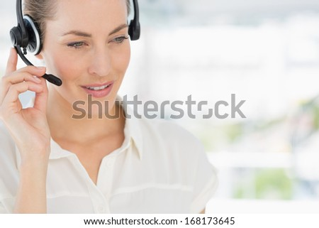 Close-up of a beautiful female executive with headset in a bright office - stock photo