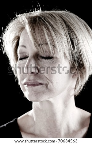 Close-up of a beautiful mature woman with eyes closed, portrait/actress on stage - stock photo