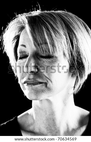 Close-up of a beautiful mature woman with eyes closed, portrait/actress on stage-black and  white image - stock photo