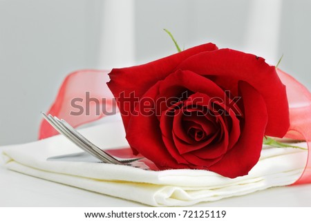 Close up of a beautiful red rose with dinnerware. Selective focus with some blur on lower portion of image. - stock photo