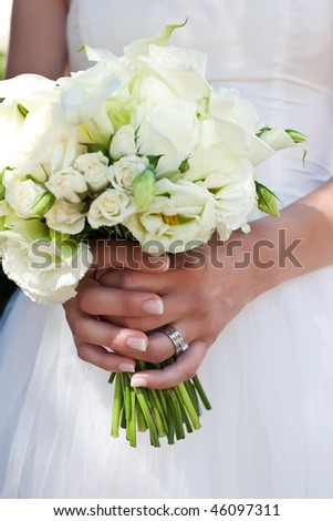 Close-up of a beautiful wedding bouquet held by the bride. - stock photo