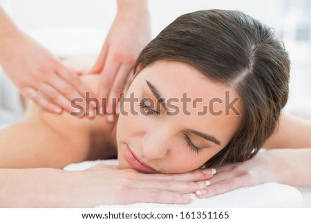 Close up of a beautiful woman enjoying shoulder massage at beauty spa