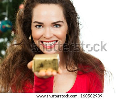 Close-up of a beautiful woman holding out a small Christmas gift towards camera, in front of a Christmas tree. Isolated on white.