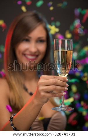 Close-up of a beautiful woman holding with champagne. Focus on foreground, on champagne. Confetti is the air.