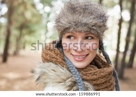 Close-up of a beautiful woman in fur hat with woolen scarf in the woods - stock photo