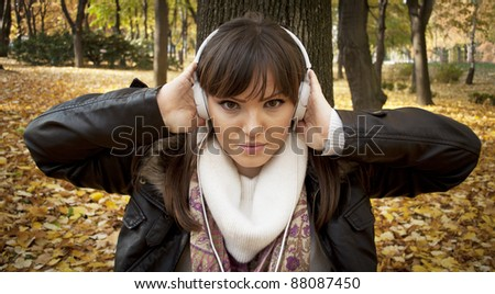 Close-up of a beautiful woman listening music outdoor - stock photo