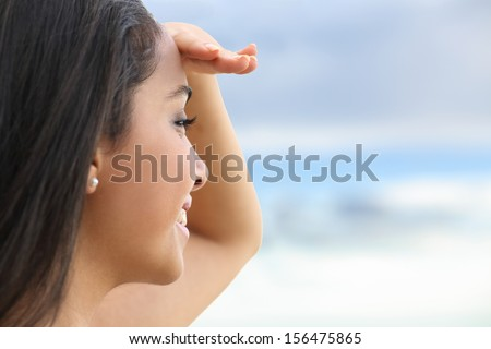 Close up of a beautiful woman looking at the horizon with a hand in forehead with the sky in the background           - stock photo