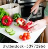 Close-up of a beautiful woman preparing a salad in the kitchen - stock photo