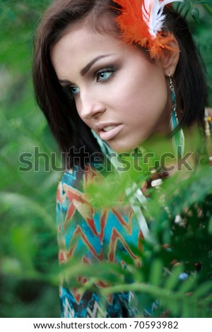 Close up of a beautiful woman sitting in the forest - stock photo