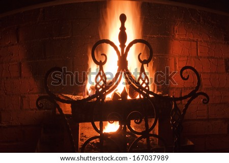 close up of a beautiful wrought-iron grate against the bright flame and a brick wall - stock photo