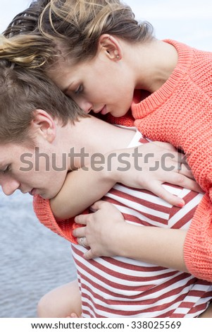 Close up of a beautiful young couple at the beach. They are wearing casual clothing and are cuddled in together.  - stock photo
