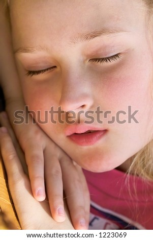 close-up of a beautiful young girl sleeping and dreaming outside in the garden