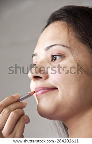 Close up of a beautiful young Indian woman applying cosmetics on lips over gray background