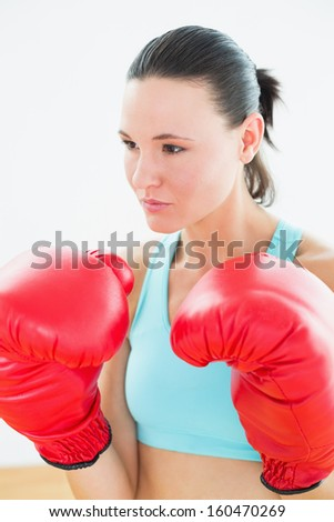 Close-up of a beautiful young woman in red boxing gloves at fitness studio