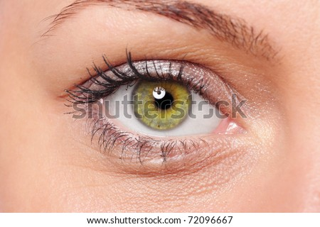Close-up of a beautiful young woman's green eye - stock photo