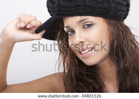 Close up of a beautiful young woman smiling wearing black hat - stock photo