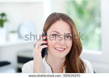 Close up of a beautiful young woman talking on phone - stock photo