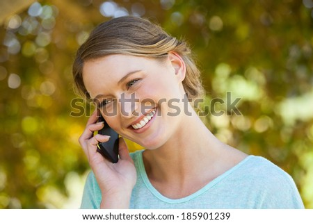Close-up of a beautiful young woman using mobile phone in the park - stock photo