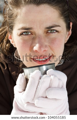 Close-up of a beautiful young woman wearing gloves, holding a cup of hot drink, smiling into camera - outdoors - stock photo