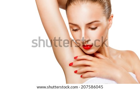 Close-up of a beautiful young woman with makeup showing her smooth armpit isolated on white background. Focus on the armpit - stock photo